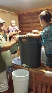 Junior Beekeeper spins the honey while his sister watches